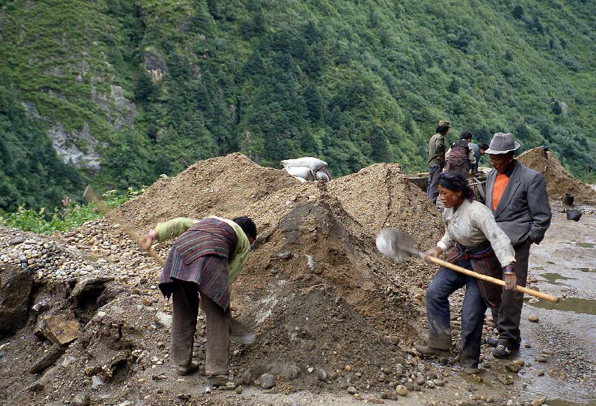 Donne tibetane al lavoro controllate da un supervisore nei pressi di Kodari
