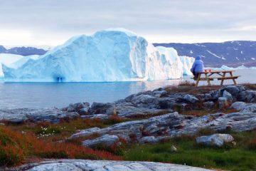 Groenlandia: donna che guarda un iceberg